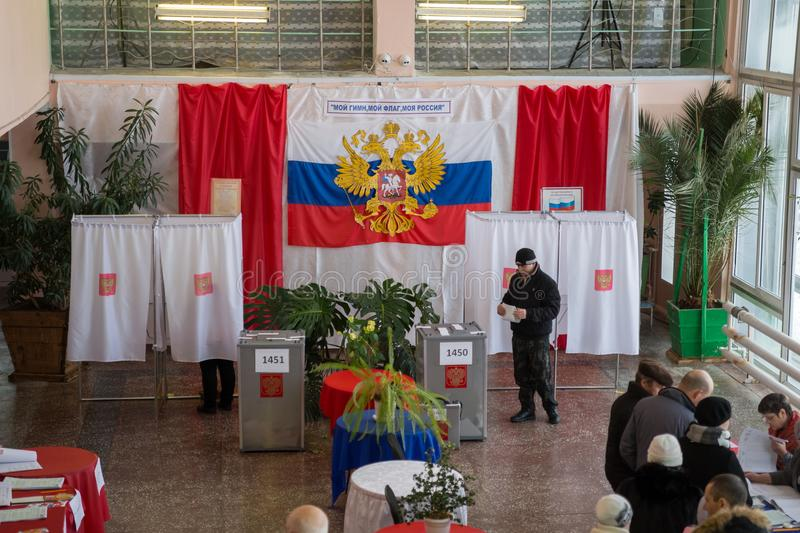 Man goes to the ballot box in the hall for voting in the Russian outback. stock photos