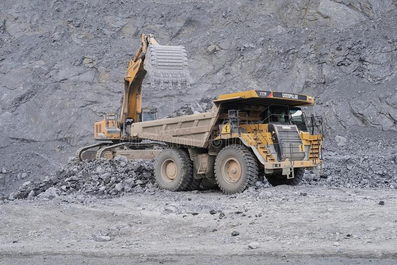 Excavator Liebherr loads ore in a dump truck Caterpillar in the background of a quarry. royalty free stock photos