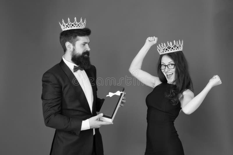 beloning man in smoking en sexy vrouw Gebaarde man en gelukkige vrouw in kroon koninklijk paar in liefde datumsucces Manier stock afbeelding