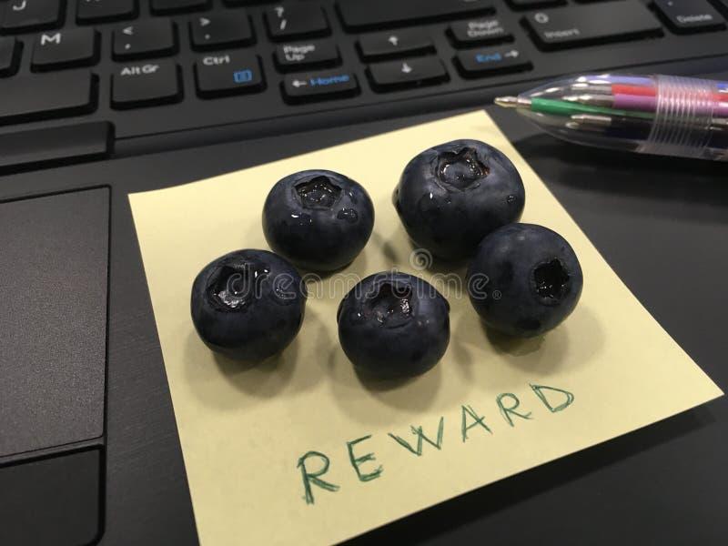 Beloning - met de hand geschreven op een post-it, op een computertoetsenbord royalty-vrije stock foto's