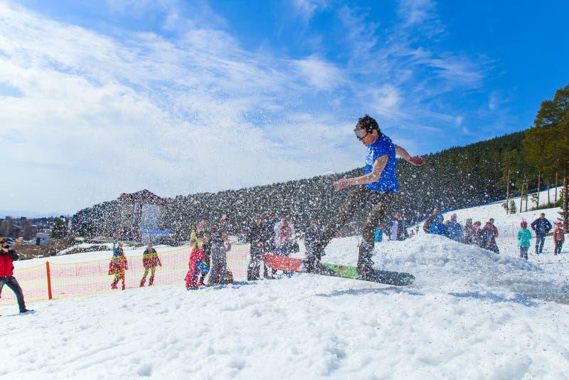 BELORETSK, RÚSSIA, O 13 DE ABRIL DE 2019 - o snowboarder do homem novo faz um salto na inclinação do esqui nas montanhas de Ural imagem de stock royalty free