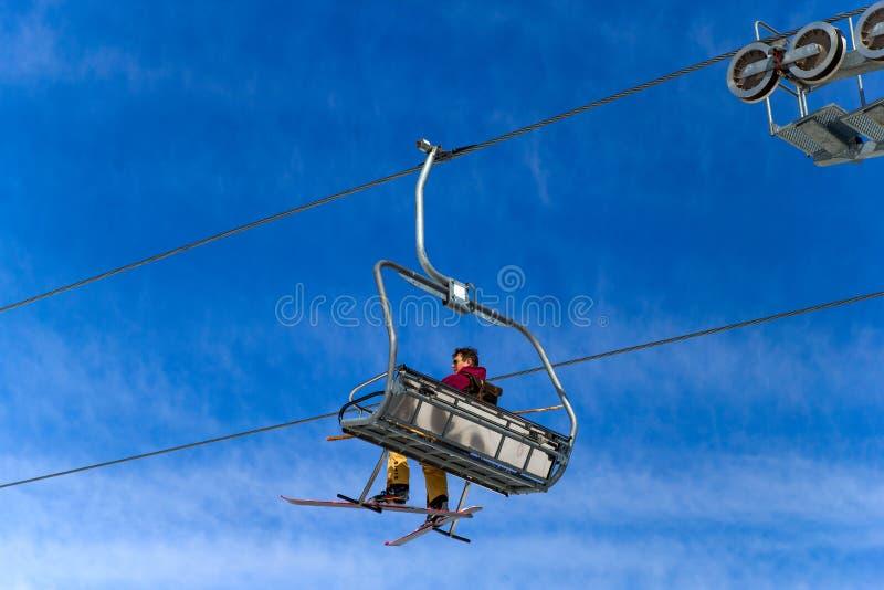 BELORETSK, RUSLAND, 13 APRIL 2019 - de mensenskiër gaat op de skilift tegen blauwe hemel, die het skiseizoen in de Ural-bergen sl royalty-vrije stock afbeeldingen