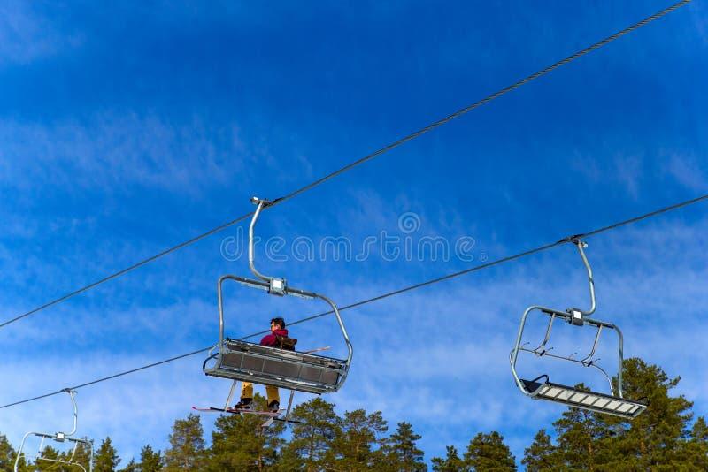 BELORETSK, RUSLAND, 13 APRIL 2019 - de mensenskiër gaat op de skilift tegen blauwe hemel, die het skiseizoen in de Ural-bergen sl stock fotografie