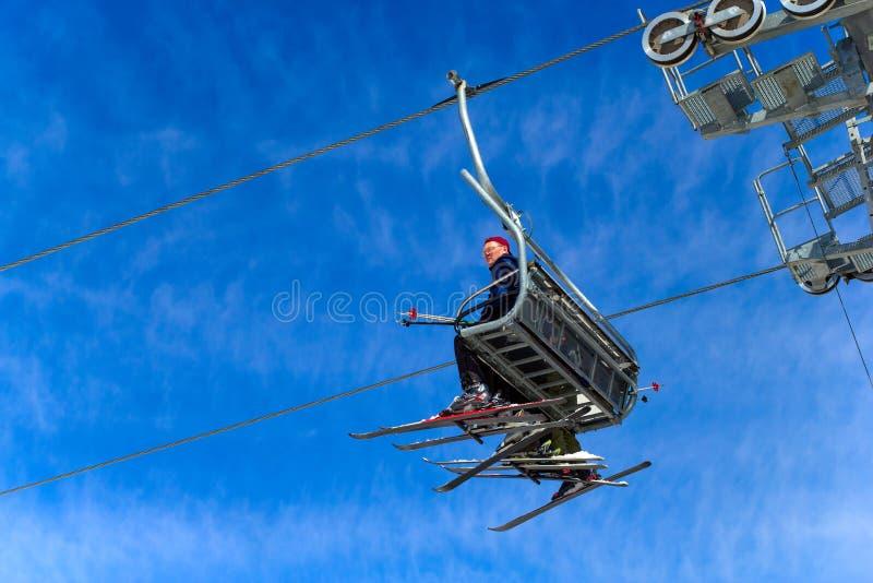 BELORETSK, RUSLAND, 13 APRIL 2019 - de mensenskiër gaat op de skilift tegen blauwe hemel, die het skiseizoen in de Ural-bergen sl stock foto