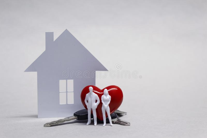 Beloved home with a married couple, a red heart and a bunch of keys on the background of a paper house. Beloved home with a married couple, a red heart and a stock image