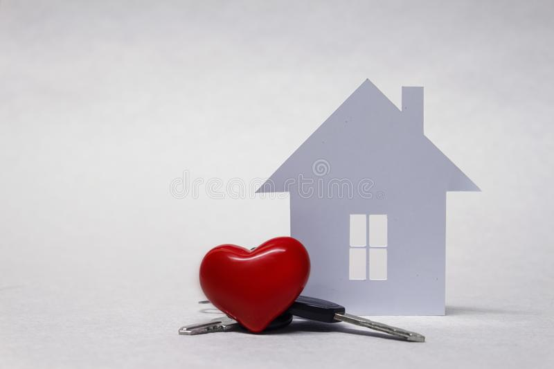 Beloved home with a red heart and a bunch of keys on the background of the house of paper. Beloved home with a red heart and a bunch of keys on the background royalty free stock image