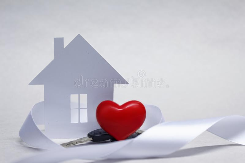 Beloved home with a red heart and a bunch of keys on the background of the house of paper. Beloved home with a red heart and a bunch of keys on the background royalty free stock photography