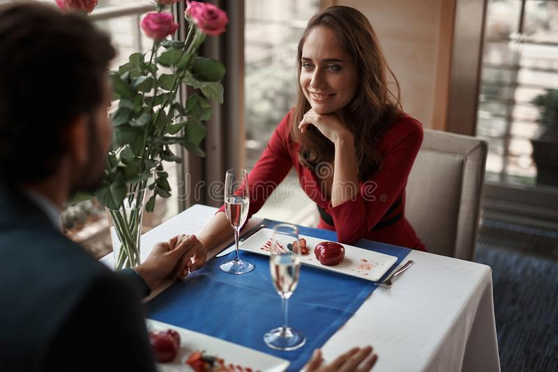 Beloved male and female having date in restaurant. Concept of lovely and romantic date. Waist up portrait of happy lady holding hands with her lover while stock images