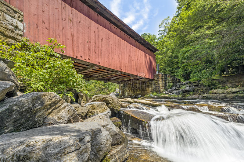 Below Packsaddle Covered Bridge. Built in 1887, the historic Packsaddle Covered Bridge crosses over a waterfall on Brush Creek in rural Somerset County royalty free stock photo
