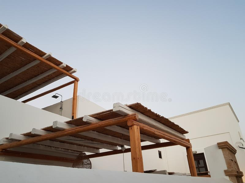 From below shot of wooden sheds near walls of white buildings on street of small town against cloudless blue sky. From below shot of wooden sheds near walls of royalty free stock photo