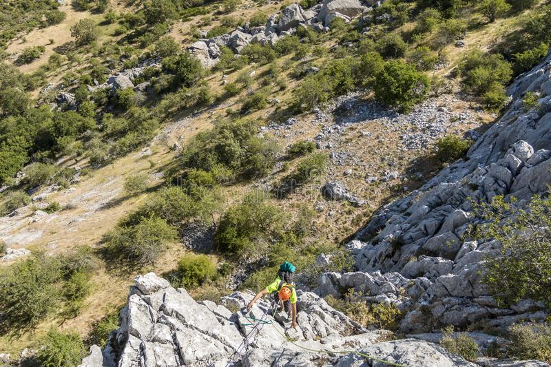 Traveler climbing on hill. From below tourist man climbing up on hill in sunny day stock images