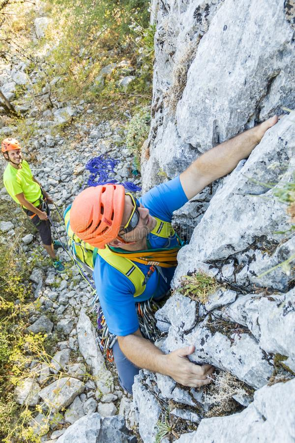Alpininsts climbing up. From below two alpinists men climbing up on hill together royalty free stock image