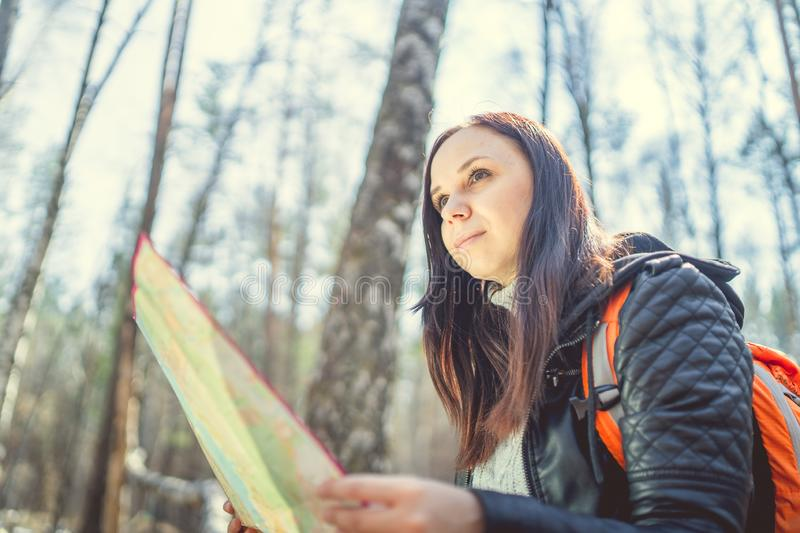 Traveling woman with map in woods From below of woman with backpack sitting on log in woods reading map in sunlight. From below of woman with backpack sitting on stock image