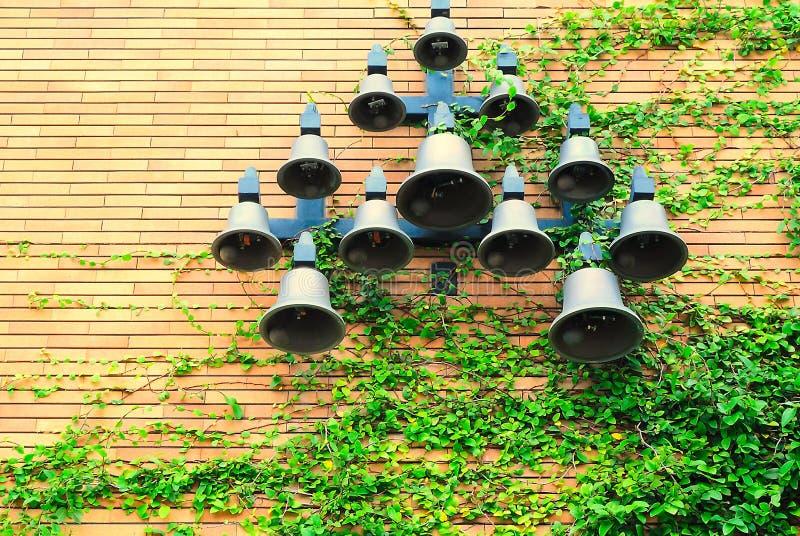 Bels são penduradas na parede escalada por plantas fotografia de stock