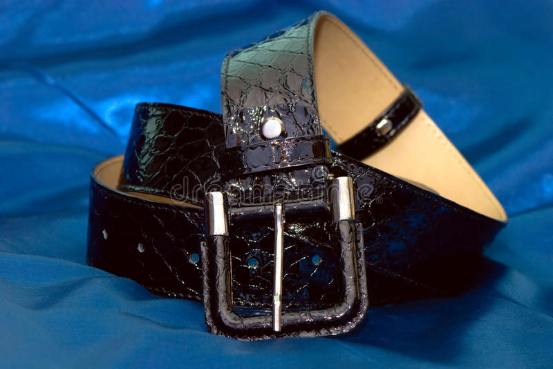 Belt. From patent leather on a blue fabric stock photo