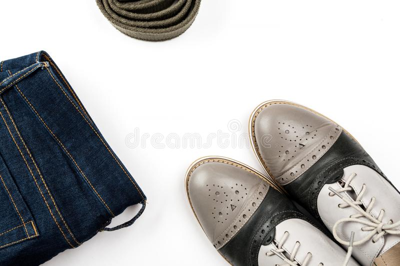 Belt, blue jeans and gray shoes on a white background top view, flat lay royalty free stock images