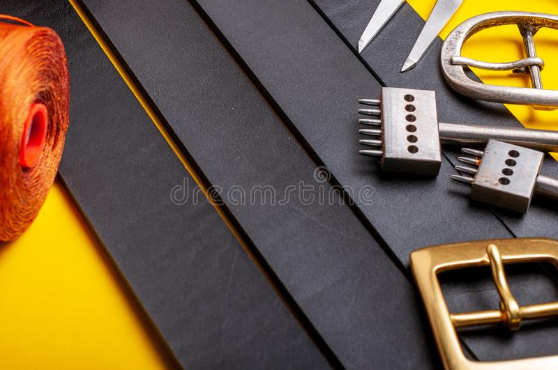 Belt buckles with leather tools on black full grain leather background. Materials, accessories on craftman`s work desk. Belt buckles with leather tools on black stock photography