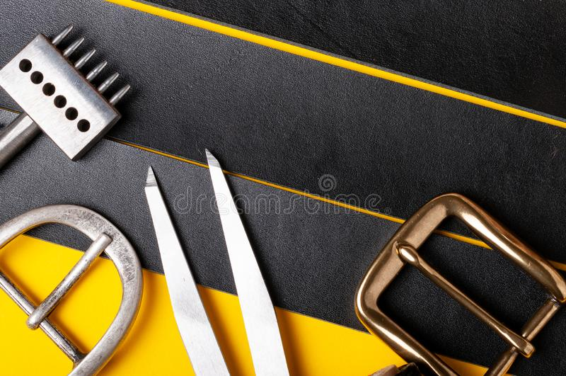 Belt buckles with leather tools on black full grain leather background. Materials, accessories on craftman`s work desk. Belt buckles with leather tools on black royalty free stock photos