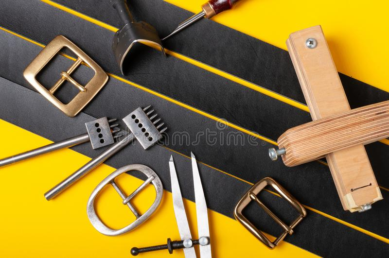 Belt buckles with leather tools on black full grain leather background. Materials, accessories on craftman`s work desk. Belt buckles with leather tools on black stock images