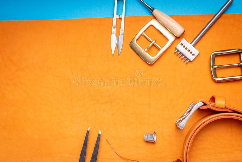 Belt buckles with leather tools on orange full grain leather background. Materials, accessories on craftman`s work desk.  royalty free stock image