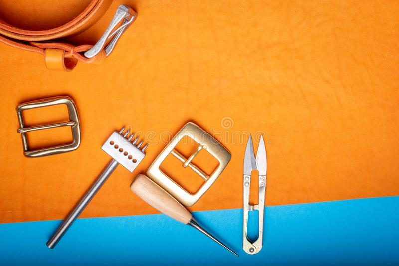 Belt buckles with leather tools on orange full grain leather background. Materials, accessories on craftman`s work desk.  stock image
