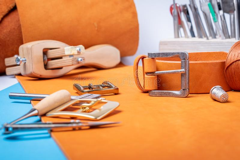 Belt buckles with leather tools on orange full grain leather background. Materials, accessories on craftman`s work desk.  royalty free stock photo