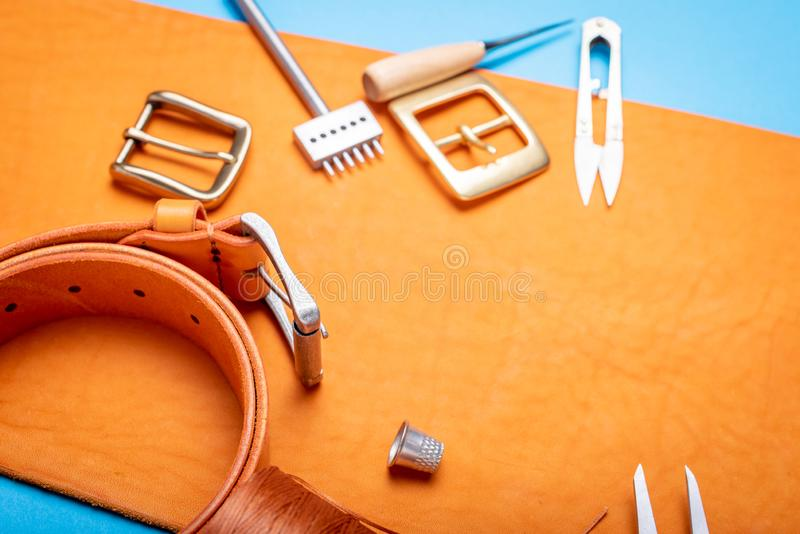 Belt buckles with leather tools on orange full grain leather background. Materials, accessories on craftman`s work desk.  royalty free stock images