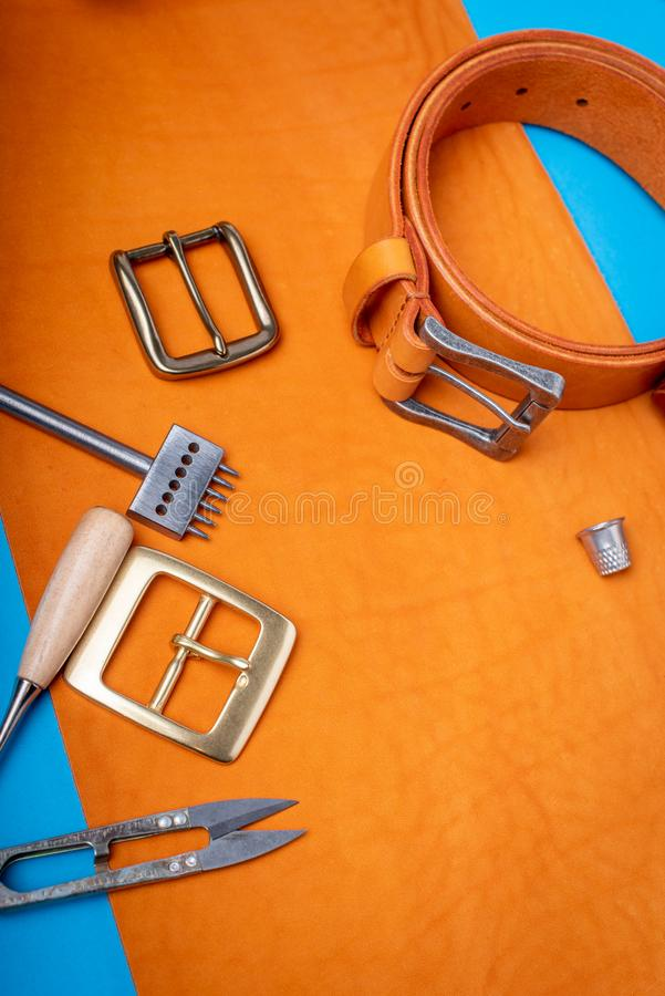 Belt buckles with leather tools on orange full grain leather background. Materials, accessories on craftman`s work desk.  stock photo