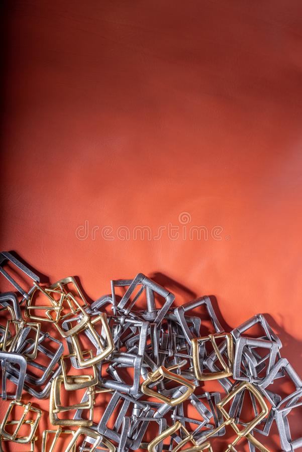 Belt buckles on red full grain leather background. Materials, accessories on leather craftman`s work desk.  royalty free stock photos