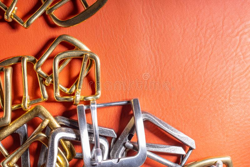 Belt buckles on red full grain leather background. Materials, accessories on leather craftman`s work desk.  royalty free stock photography