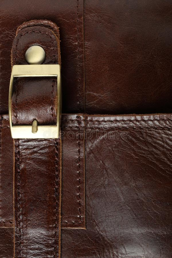 Belt with yellow metal clasp on a brown leather bag royalty free stock photos