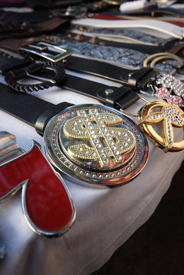 Belts and buckles at market. A closeup view of leather belts and fancy, decorated buckles for sale on an open market table stock photos