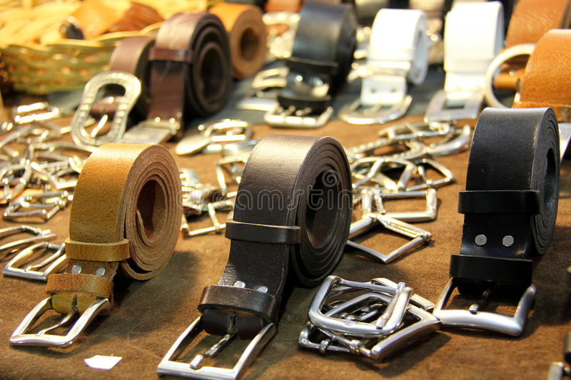 Belts and buckles. For sale on a market stool stock image