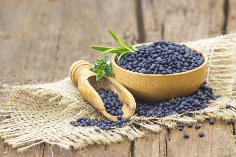 Beluga lentils and herbs. On wooden background stock photos