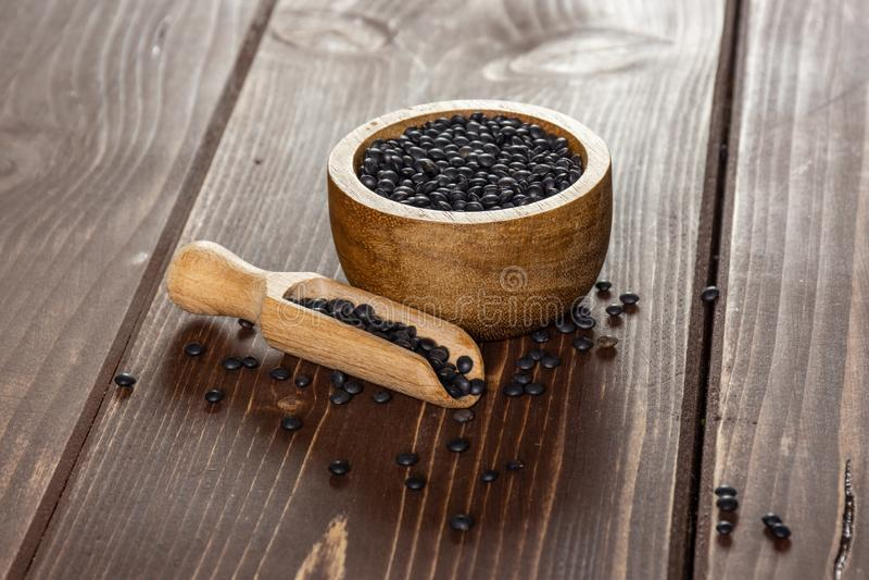 Beluga nero delle lenticchie su legno marrone immagine stock