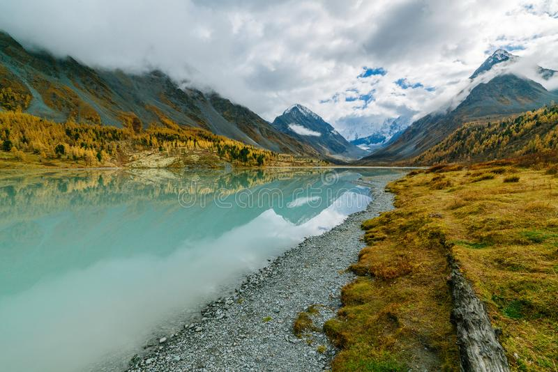 View from lake Akkem on mountain Belukha near board between Russia and Kazakhstan during golden autumn. Belukha Mountain covered with snow is reflected in a stock photo