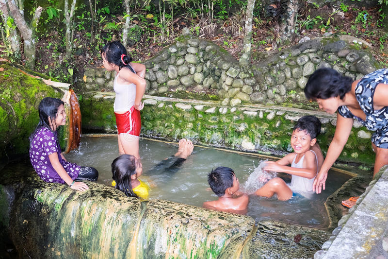 Children are swimming and playing at Hot Springs pool near Belulang village stock photo
