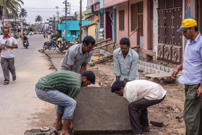 Four guys handle heavy concrete plate, Belur Karnataka India royalty free stock images