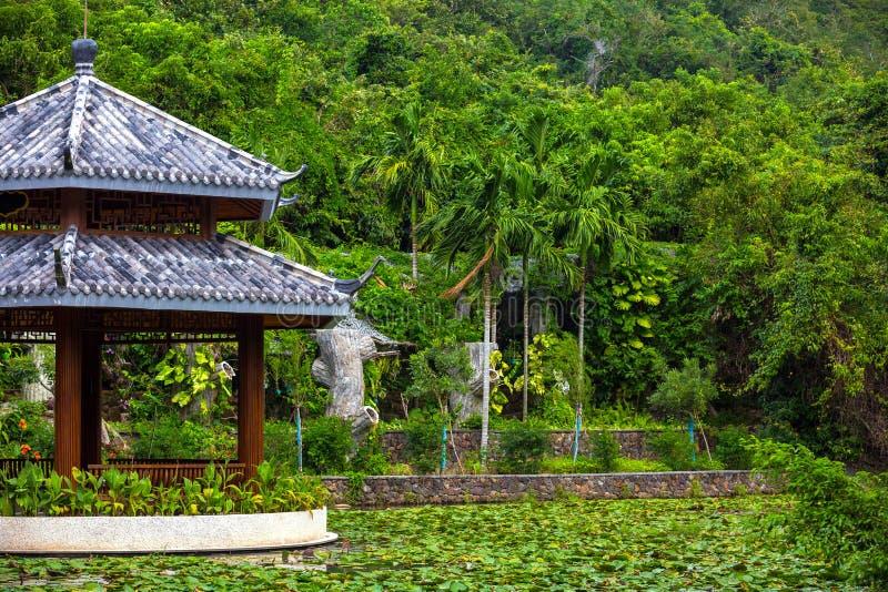 Belvédère chinois sur un étang, pointillé avec des nénuphars Baie T de Yalong photo libre de droits