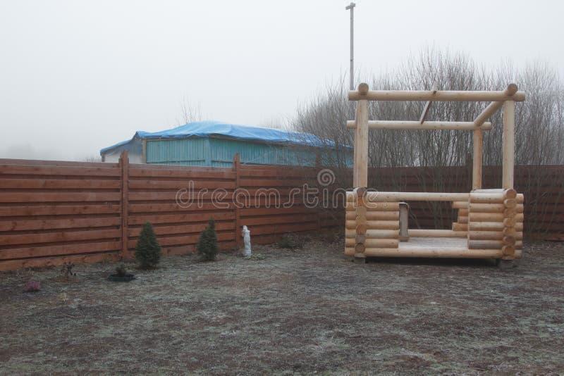 Belvédère de rondin dans le jardin congelé en brume photographie stock libre de droits