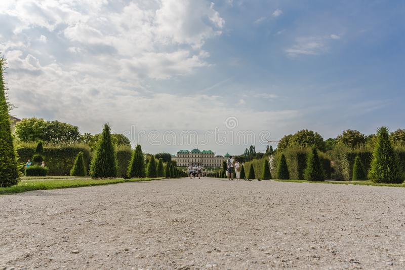 The Belvedere Garden with trimmed plants, decorated with carved sculptures. View on Upper Belvedere palace with park alley in. The large Belvedere Garden in stock photography