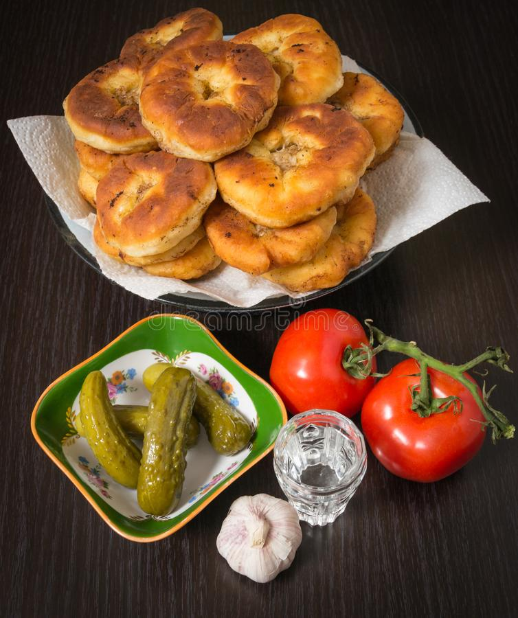 Belyashi, Tomaten, Ingelegde komkommers, Knoflook, Wodkaglas royalty-vrije stock afbeeldingen