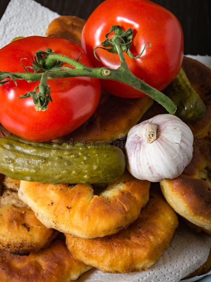 Belyashi, Tomaten, Ingelegde komkommers, Knoflook, Wodkaglas stock foto's