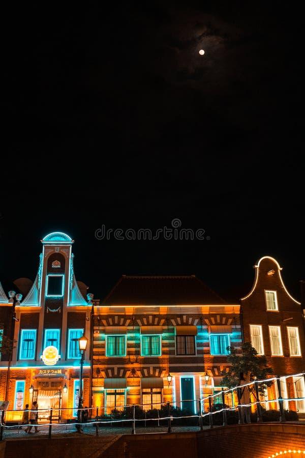 Belysningbyggnad och måne i himlen royaltyfri foto