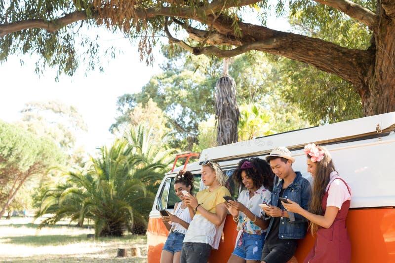 Belzebuby używa smartphones podczas gdy stojący obozowicza samochodem dostawczym obraz royalty free