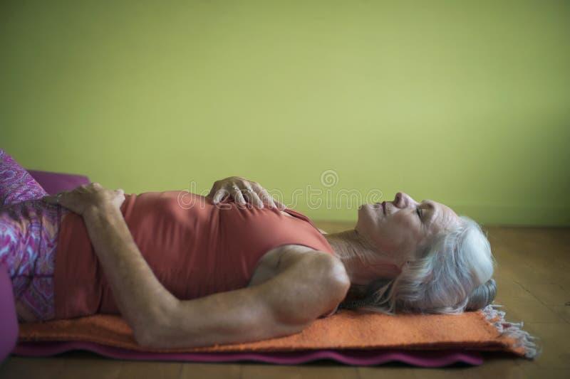 Bem-estar superior do coração da mulher da ioga restaurativa imagem de stock