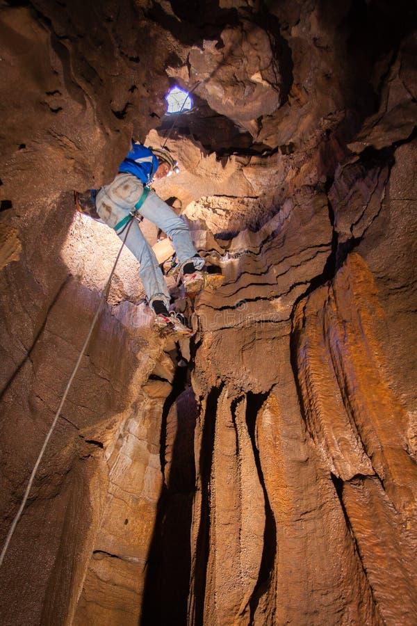 Bemanna att stiga ned in i grottan royaltyfria foton