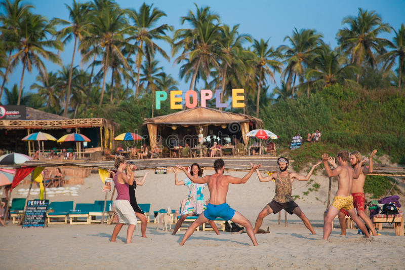 Bemanna och två kvinnor som övar yoga på en vitbakgrund arkivfoton