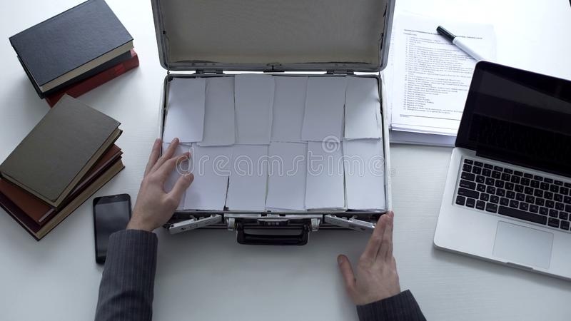 Bemannen Sie Öffnungsaktenkoffer mit Papieren anstelle des Geldes, Geschäftsbetrug, Fälschung lizenzfreie stockfotografie