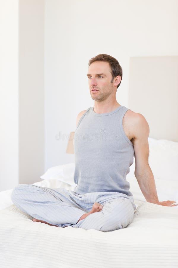 Bemannen Sie übendes Yoga auf seinem Bett lizenzfreies stockbild